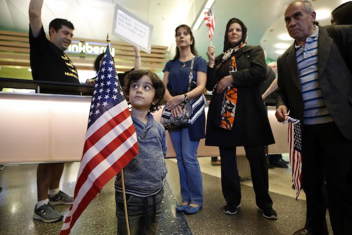 Three-year-old Shayan Ara holds an American flag as protests against President Donald Trump's executive order banning travel from seven Muslim-majority countries continue at Los Angeles International Airport Sunday, Jan. 29, 2017. (AP Photo/Ryan Kang)