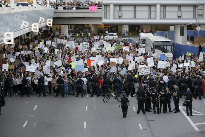 Police officers block demonstrators from marching on the lower roadway as protests against President Donald Trump's executive order banning travel from seven Muslim-majority countries continue at Los Angeles International Airport Sunday, Jan. 29, 2017. (AP Photo/Ryan Kang)