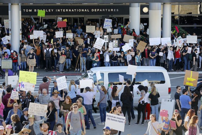 Demonstrators hold signs outside of Tom Bradley International Terminal as protests against President Donald Trump's executive order banning travel from seven Muslim-majority countries continue at Los Angeles International Airport Sunday, Jan. 29, 2017. (AP Photo/Ryan Kang)