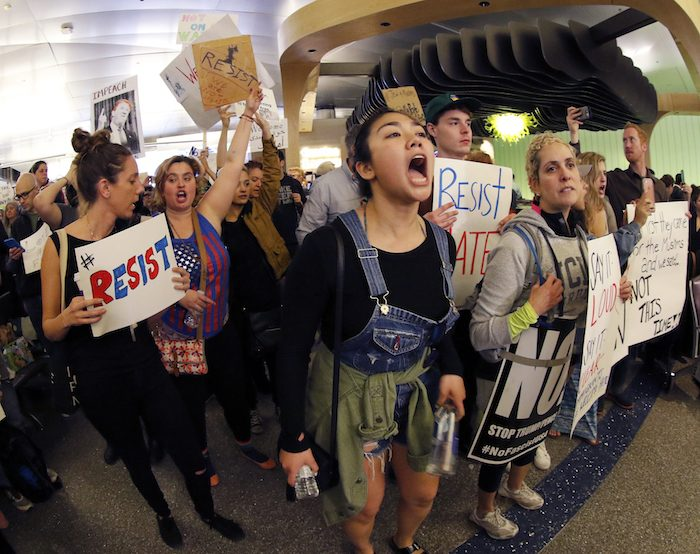 Demonstrators chant inside Tom Bradley International Terminal as protests against President Donald Trump's executive order banning travel from seven Muslim-majority countries continue at Los Angeles International Airport Sunday, Jan. 29, 2017. (AP Photo/Ryan Kang)