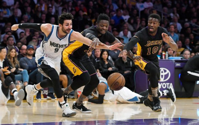 Minnesota Timberwolves guard Ricky Rubio, left, of Spain, scrambles for a loose ball along with Los Angeles Lakers forward Julius Randle, center, and guard David Nwaba during the first half of an NBA basketball game, Friday, March 24, 2017, in Los Angeles. (AP Photo/Mark J. Terrill)