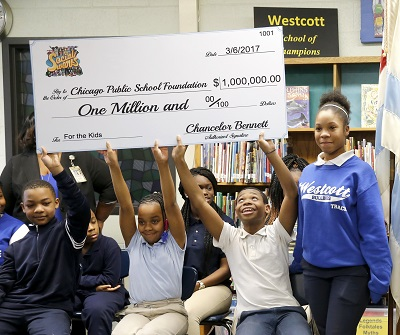Students at the Westcott Elementary School on Chicago's South Side holds up a check, a gift of $1 million to the Chicago Public School Foundation, from Chance The Rapper during a news conference at the school Monday, March 6, 2017, in Chicago. The Grammy-winning artist is calling on Illinois Gov. Bruce Rauner to use executive powers to better fund Chicago Public Schools. (AP Photo/Charles Rex Arbogast)
