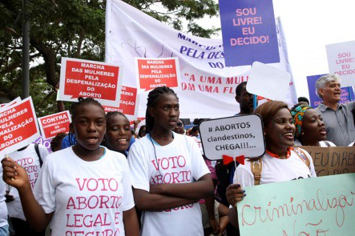 Hundreds of Angolans hold placards and shout slogans as they march to protest against a draft law that would criminalise all abortion on March 18, 2017 in Luanda, Angola.  The proposed new penal code has been sharply criticised by many, including Isabel dos Santos, reported to be the richest woman in Africa and the daughter of veteran strongman President Jose Eduardo dos Santos.  / AFP PHOTO / AMPE ROGERIO