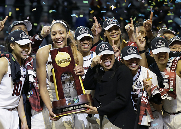 South Carolina forward A'ja Wilson holds the trophy and coach Dawn Staley points as the team celebrates a win over Mississippi State in the final of NCAA women's Final Four college basketball tournament, Sunday, April 2, 2017, in Dallas. South Carolina won 67-55. (AP Photo/Tony Gutierrez)