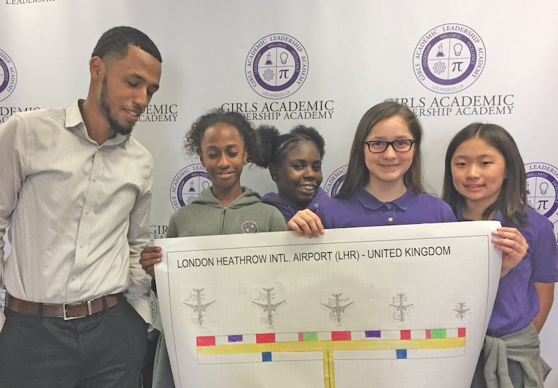 Middle-school students from the Girls Academic Leadership Academy and their group leader (left) display their design of a terminal for London's Heathrow Airport. (Courtesy Photo)