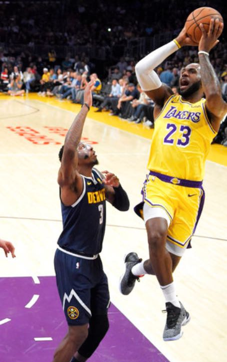 51dd65c11c3f0 Los Angeles Lakers forward LeBron James, right, shoots and makes his first  two points of the game as Denver Nuggets forward Torrey Craig defends  during the ...